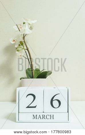 Closeup white wooden calendar with black 26 march word with white orchid flower on white wood desk and cream color wallpaper in room textured background selective focus at the calendar