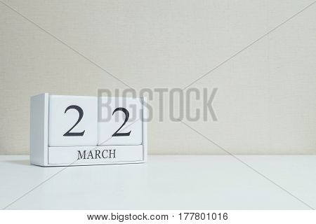 Closeup white wooden calendar with black 22 march word on blurred white wood desk and cream color wallpaper in room textured background with copy space selective focus at the calendar
