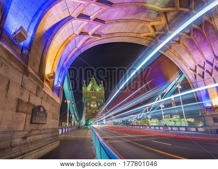 London England - Night shot of the world famous colorful Tower Bridge in London with double decker bus light trails and offices and Shard skyscraper at background