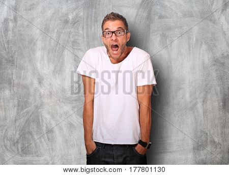 Surprise of the young man in white t-shirt and jeans