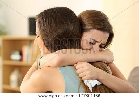 Girl embracing to comfort to her sad best friend after break up sitting on a couch in the living room at home