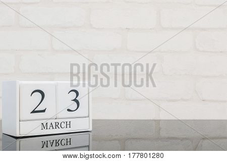 Closeup white wooden calendar with black 23 march word on black glass table and white brick wall textured background with copy space selective focus at the calendar