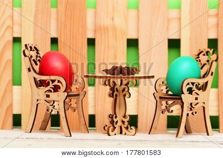 Easter Egg In Wooden Chairs At Table With Badian