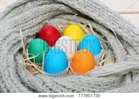Painted Easter Colorful Eggs With Straw Nest In Grey Scarf