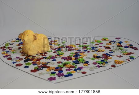 A multi-colored candy is divided into a heart symbol drawn on a white background and on top is a lamb figure as a symbol of wishes cares and Easter feasts.