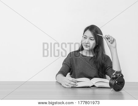 Closeup asian woman tired from reading a book with thinking face emotion in work concept on wood table and white cement wall textured background in black and white tone with copy space