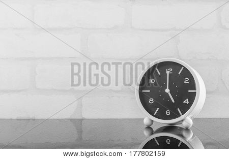 Closeup black and white alarm clock for decorate in 5 o'clock on black glass table and white brick wall textured background in black and white tone with copy space