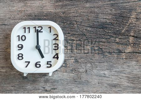 Closeup white clock for decorate in 5 o'clock on old wood floor textured background with copy space