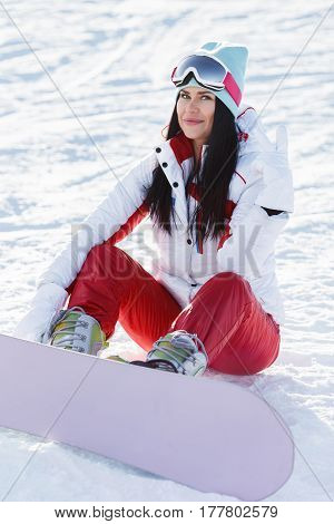 Girl with snowboard on background of winter mountain landscape