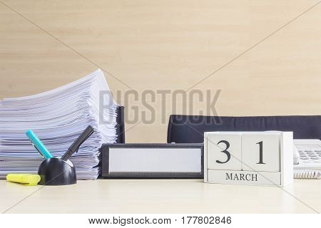 Closeup white wooden calendar with black 31 march word on blurred brown wood desk and wood wall textured background in office room view with copy space selective focus at the calendar