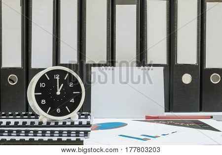 Closeup white clock for decorate in 1 o'clock desk of officer with work paper and document file in office room textured background in work concept