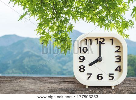 Closeup white clock for decorate in 8 o'clock on blurred mountain view background