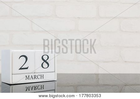Closeup white wooden calendar with black 28 march word on black glass table and white brick wall textured background with copy space selective focus at the calendar