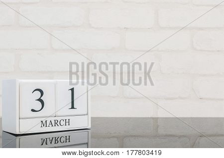Closeup white wooden calendar with black 31 march word on black glass table and white brick wall textured background with copy space selective focus at the calendar