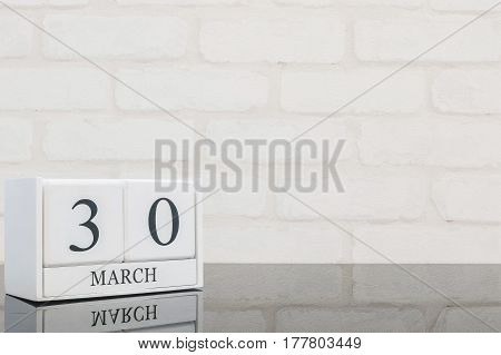 Closeup white wooden calendar with black 30 march word on black glass table and white brick wall textured background with copy space selective focus at the calendar