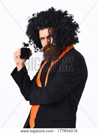 Caucasian Hipster In Suit And Black Curly Wig Holding Perfume