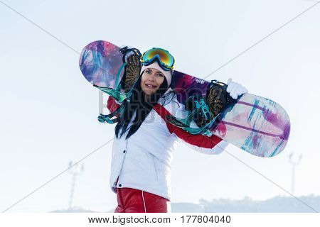 Photo of long-haired brunette in ski suit with snowboard on mountain slope