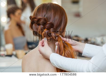 Beautiful red-haired hairy girl hairdresser weaves a French braid close-up in a beauty salon. Professional hair care and creating hairstyles.