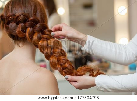 Beautiful with long red-haired hairy girl hairdresser weaves a French braid close-up in a beauty salon. Professional hair care and creating hairstyles.