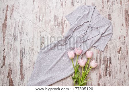 Gray dress with tie pink tulips. Wooden background top view