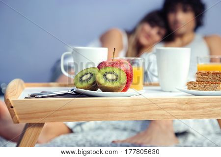 Closeup of fruit pieces in a healthy breakfast served on tray and a happy couple in love hugging in the background. Healthy food and home lifestyle concept.