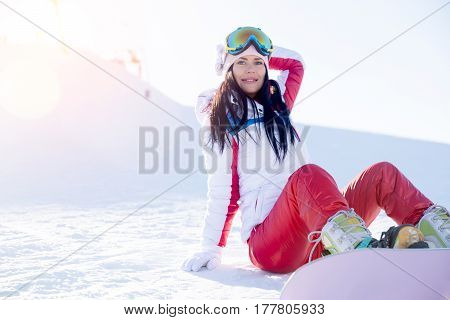 Girl in glasses with snowboard on mountain in winter