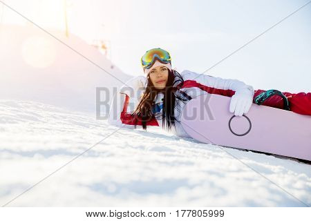 Sport brunette with snowboard in winter at mountains