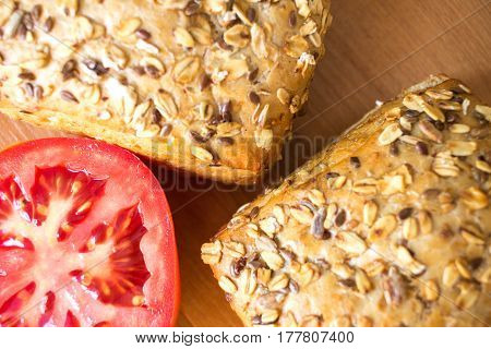 Composition Of Whole Grain Bread Buns And Red Fresh Cut In Half Tomato On Wooden Table Background