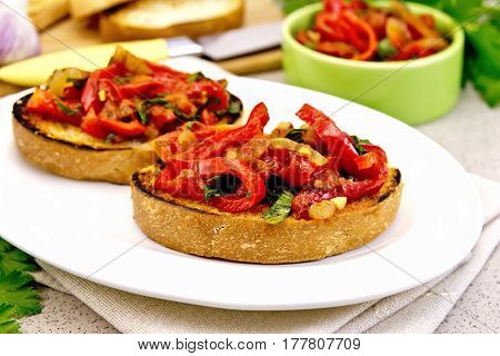Bruschetta with roasted tomatoes, peppers, garlic, onions and parsley in a white plate on a napkin on a background granite table