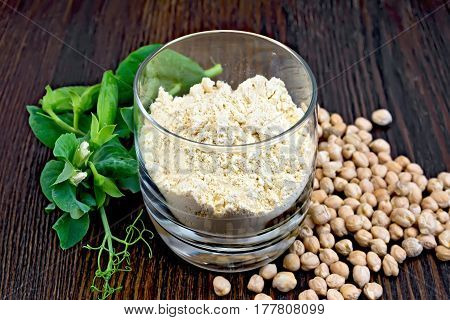 Flour chickpeas in glassful, pods of green beans and chick-pea on a dark wooden board