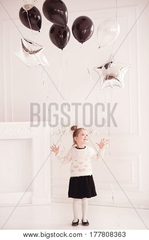 Cute baby girl 4-5 year old playing with helium in room. Wearing knitted sweater and black skirt. Birthday party.
