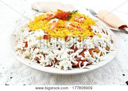Layered salad of salmon, squid, shrimp, avocado, rice and eggs in a dish on the background light wooden boards