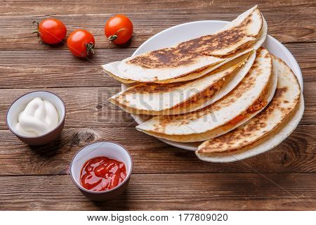 Tortillas with meat and dressing on wooden table