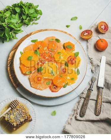 Fresh mixed citrus fruit salad with mint and honey on white ceramic plate over grey marble background, selective focus. Vegan, vegetarian, healthy, dieting, detox food, clean eating concept