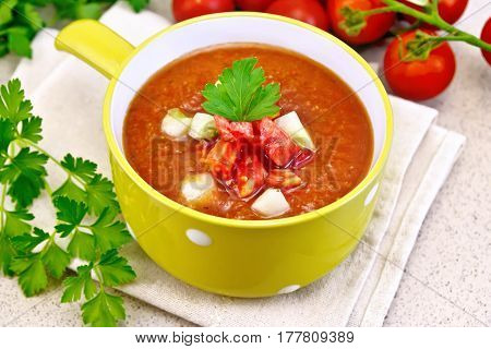 Gazpacho tomato soup in yellow bowl with parsley and vegetables on a towel on the background of a granite table