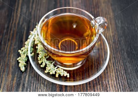 Herbal tea from wormwood in a glass cup on a saucer on a dark wooden board