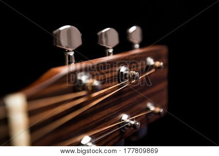 The upper part of the guitar on a black background with the strings, nut and tuning pegs, dark wood, blur