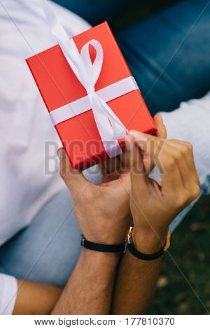 Detail Of Couple Hands Opening A Present In A Red Box