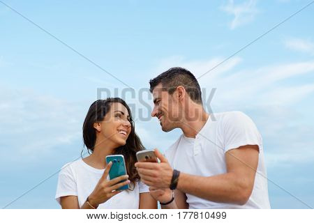 Young Couple Dating And Using Smartphones Together