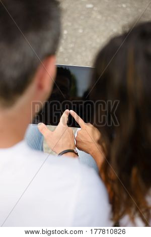 Couple Using Digital Tablet For Internet Browsing Outside