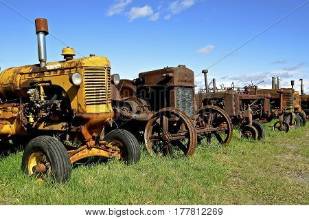 A row of old rusty worn tractors stand  in a row bringing back old farming memories.