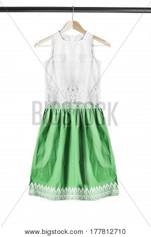 White and green lacy dress on wooden clothes rack isolated over white