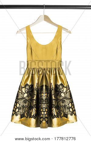 Yellow satin mini dress on wooden clothes rack isolated over white