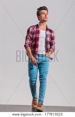 walking young casual man looking up to side on grey studio background