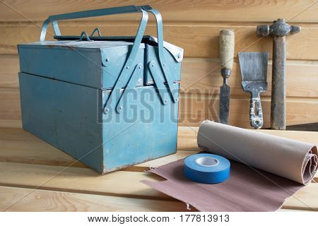 Tool box and tools on a wooden background