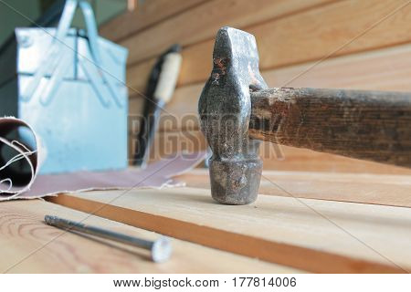 Hammer nail and tool box on a wooden background