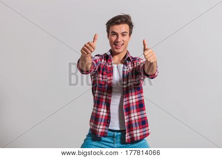 happy young casual man making the ok thumbs up sign on grey background