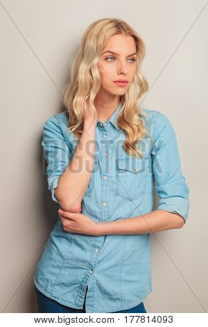 blonde casual woman holding hand on neck and looks away to a side in studio