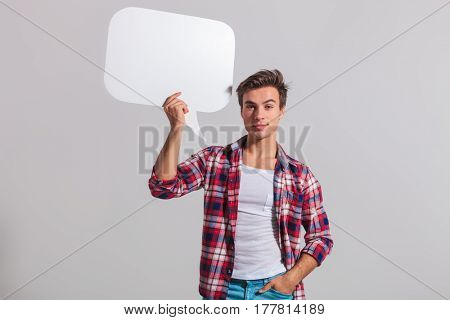 young casual man holding speech bubble in studio on grey background