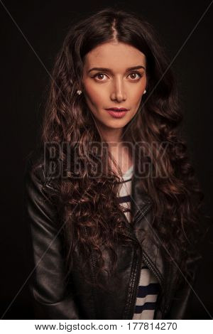 portrait of a young beautiful woman in leather jacket on black studio background